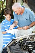 Father teaching his son how to check the oil on the family car.