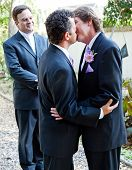 Two grooms kiss eachother in front of the minister at their gay marriage ceremony.