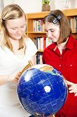 Teen school girls using a globe for research in the library.