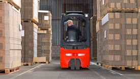 pic of forklift  - Expreinced forklift driver is driving his forklift backwards trough piled pallets with  cardboardboxes stack on it - JPG
