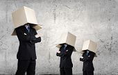 Unrecognizable businessman in suit wearing carton box on head