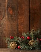 Fir branch with Christmas decoration on old wooden plank. Focus  on   Christmas decorations and fir branch