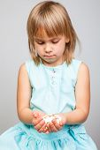 Little girl holding heap of tablets in her hands, focus on tablets