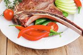 meat food : grilled beef spare rib on white dish with thyme pepper and tomato on wooden table