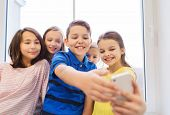 education, elementary school, drinks, children and people concept - group of school kids taking selfie with smartphone in corridor