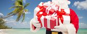 christmas, holidays, travel and people concept - close up of santa claus with gift boxes over tropical beach background