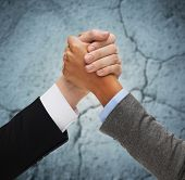 business, people and competition concept - close up of two people hands armwrestling over concrete wall background