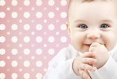childhood, people and happiness concept - smiling baby girl face over pink and white polka dots pattern background