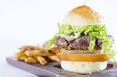 foto of hamburger  - delicious homemade hamburger with fries on a wooden board  - JPG