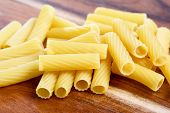Dry italian pasta penne on wooden board