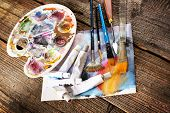 Professional acrylics paints in tubes, palette with artistic putty knife and brushes on canvas