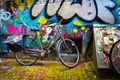 AMSTERDAM - AUGUST 31: Traditional dutch bicycle parked near brick wall painted with graffiti on August 31, 2014 in Amsterdam.