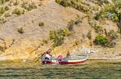 ISLA DEL SOL, BOLIVIA, MAY 7, 2014: Local people sit on mooring fishing boats at Isla del Sol shore on Titicaca lake
