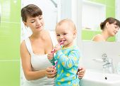 mother with child girl brushing teeth