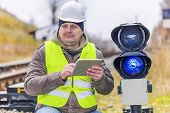 Railway employee with tablet PC near the warning lights