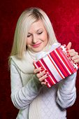 A Girl In A White Sweater And Striped Gift With White Bow