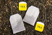 image of tea bag  - close up of background with dried black tea and two tea bags - JPG