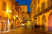 Silhouettes of people walking on evening streets of Alba in Piedmont, Northern Italy.