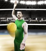Volleyball player on green uniform on volleyball court.