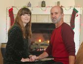 pic of cozy hearth  - A Married Couple Sit in Front of a Fireplace at Christmas  - JPG