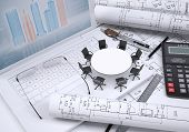 Round table, scrolled drawing, glasses, laptop, calculator and a few other tools, architectural draw