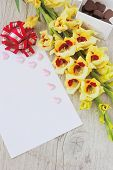 foto of gladiolus  - blank sheet of paper yellow gladioluses and chocolate candies on a wooden background - JPG