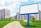 Blank billboard by road running through green hills towards city