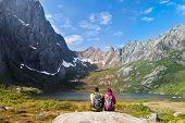 Young tourist couple sitting on stone near mountain lake