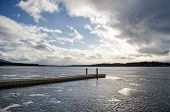 picture of dock a pond  - A lonely dock under a bright blue and cloudy sky