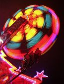 picture of carnival ride  - The spinning of the ride along with a slow shutter speed gives a blurred effect - JPG