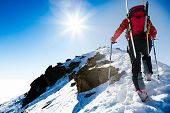 image of dangerous  - Mountaineer walking up along a snowy ridge with the skis in the backpack - JPG