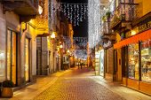 ALBA, ITALY - DECEMBER 06, 2012: Pedestrian street in old town illuminated and decorated for Christmas and New Year holidays. This area is very popular with locals and tourists visiting Alba.