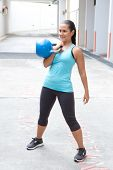 Beautiful hispanic woman in blue sports attire demonstrating the clean pose with a blue kettlebell, outdoor.