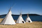 stock photo of teepee  - Three teepees are lined up in a row in front of water - JPG