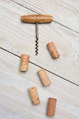 Closeup of an antique cork screw and five used corks on a rustic whitewashed wood table. Vertical format from a high angle.