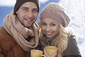 Closeup photo of happy loving couple drinking tea at wintertime outdoors.