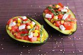 Tasty salad in avocado on bamboo napkin close-up
