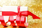 White gift box with red ribbon on golden glitter background
