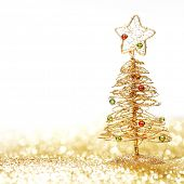 Toy golden decorative Christmas tree on glitter background