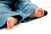 stock photo of cute baby  - Close up of baby feet and jeans isolated.