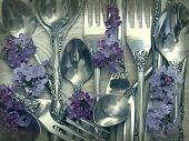 forks and spoons with flowers on the table,