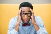 stock photo of dork  - Closeup portrait stunned nerd young man hands on head open mouth jaw drop with bow tie and big glasses isolated yellow background - JPG