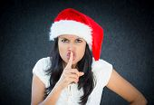 stock photo of shh  - Closeup portrait of a cute christmas woman with a red santa claus hat white dress finger on mouth saying shh be quiet - JPG