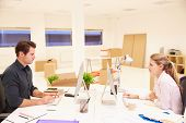 Businesspeople Working At Desks In New Office