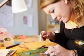 stock photo of jewelry  - Young Woman Making Jewelry At Home - JPG