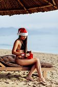 Santa Girl In Bikini  Unpacking Christmas Gift