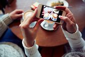 Two cups of cappuccino, cheesecake and small giftbox on cellphone display