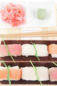 Japanese traditional cuisine - Different Types of Nigiri Sushi : Tuna (maguro) Salmon (sake) and Eel (unagi) with Wasabi and Ginger on bamboo mat isolated over white background