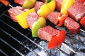 fresh raw beef shish kebab with pepper chunk on black big grill bbq