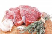 picture of flesh  - fresh raw beef meat fillet flesh with peppercorn and thyme ready to grill on wood figured old style board isolated over white background - JPG
